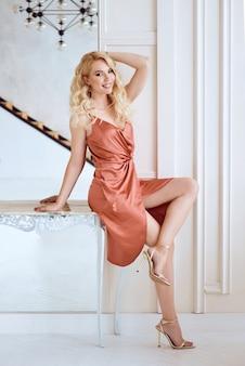 Kaukasische trendige frau im braunen kleid sitzt am spiegel auf dem tisch im modernen wohnzimmer