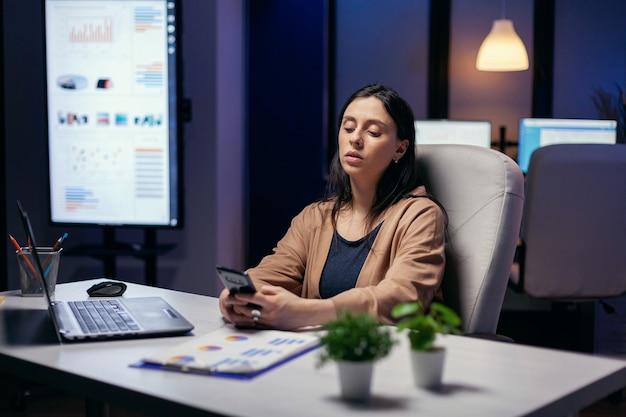 Kaukasische unternehmernachrichten während der arbeit am abend. geschäftsfrau, die spät in der nacht sms schreibt, während sie mit dem smartphone an einem wichtigen projekt arbeitet.
