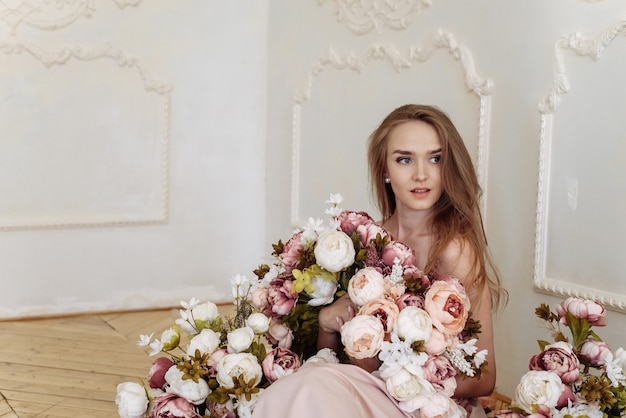Kaukasische weiße frau der jungen dame mit blonder hochhackiger frisur und nackten schultern, die mit verschiedenen farben aufwerfen
