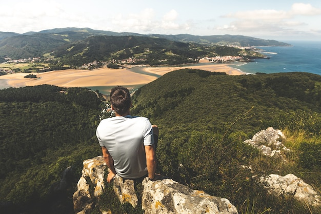 Kaukasischen jüngling auf der spitze eines berges mit blick auf urdaibai rivermouth neben dem kantabrischen meer, in bizkaia; baskenland.