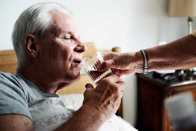 Kaukasischer älterer mann trinkwasser in seinem bett