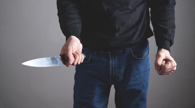 Kaukasischer aggressiver mann, der mit faust droht und messer hält.