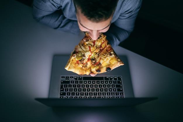 Kaukasischer angestellter, der pizza isst und laptop betrachtet, während er spät in der nacht im büro sitzt.