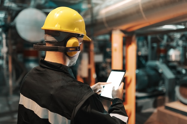 Kaukasischer arbeiter in der schwerindustrieanlage mit helm und in uniform unter verwendung der tablette für die arbeit.