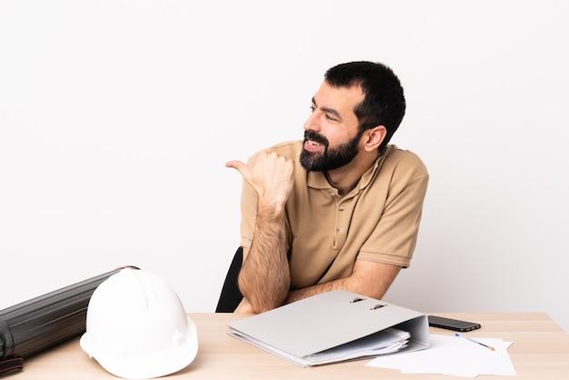 Kaukasischer architekt mit bart in einem tisch, der auf die seite zeigt, um ein produkt zu präsentieren.