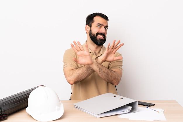Kaukasischer architektenmann mit bart in einer nervösen tabelle, die hände nach vorne streckt