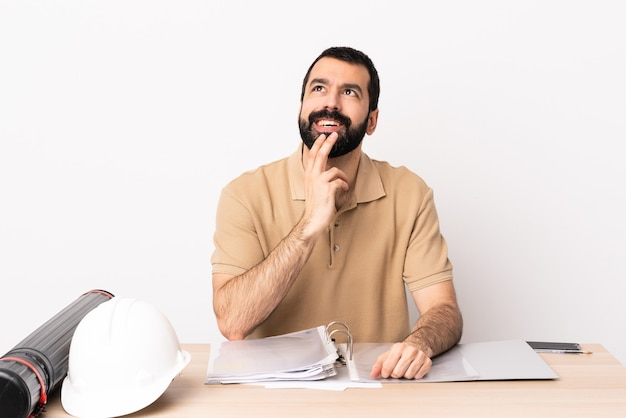 Kaukasischer architektenmann mit bart in einer tabelle, die beim lächeln nach oben schaut.