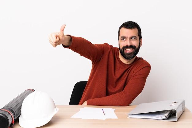 Kaukasischer architektenmann mit bart in einer tabelle, die eine daumen hoch geste gibt