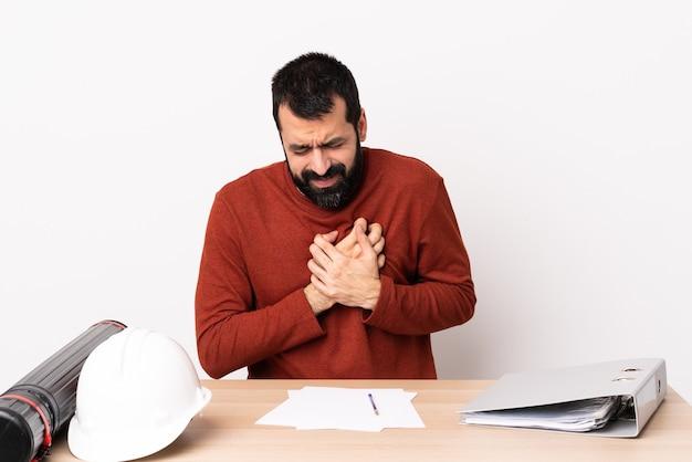 Kaukasischer architektenmann mit bart in einer tabelle, die einen schmerz im herzen hat