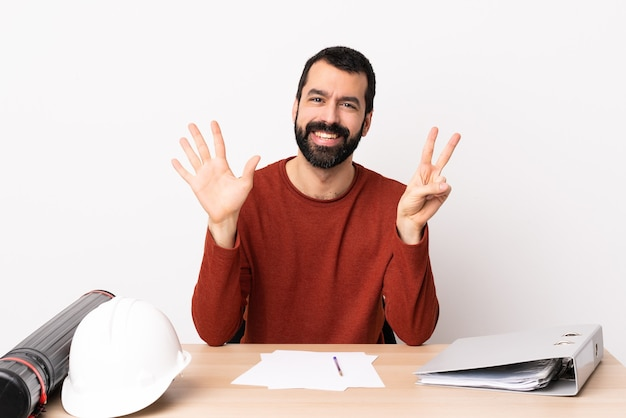 Kaukasischer architektenmann mit bart in einer tabelle, die sieben mit den fingern zählt.