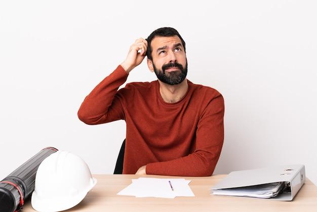 Kaukasischer architektenmann mit bart in einer tabelle, die zweifel beim kratzen des kopfes hat