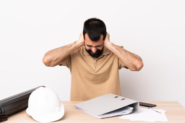 Kaukasischer architektenmann mit bart in einer tabelle frustriert und ohren bedeckend