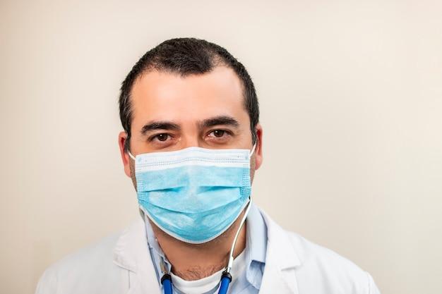Kaukasischer arzt mit stethoskop und gesichtsmaske