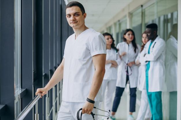 Kaukasischer arztmann, der im korridor des krankenhauses steht