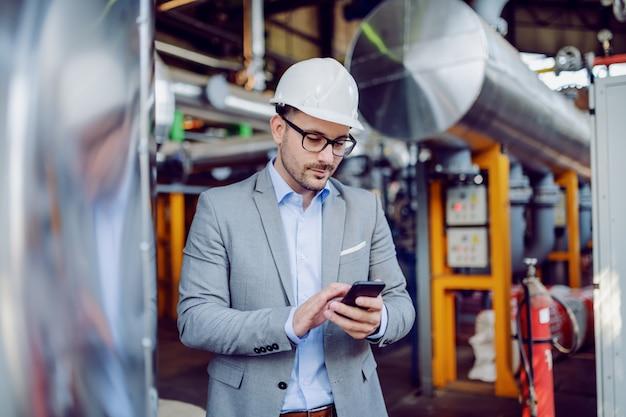 Kaukasischer aufseher im anzug und mit schutzhelm auf dem kopf unter verwendung des smartphones, während er im kraftwerk steht.