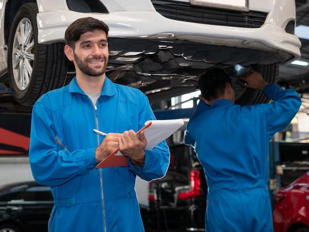 Kaukasischer automechaniker in der uniform, die zwischenablage des dienstauftrags hält, der in der garage arbeitet. techniker checkliste für reparaturmaschine ein auto in der garage.