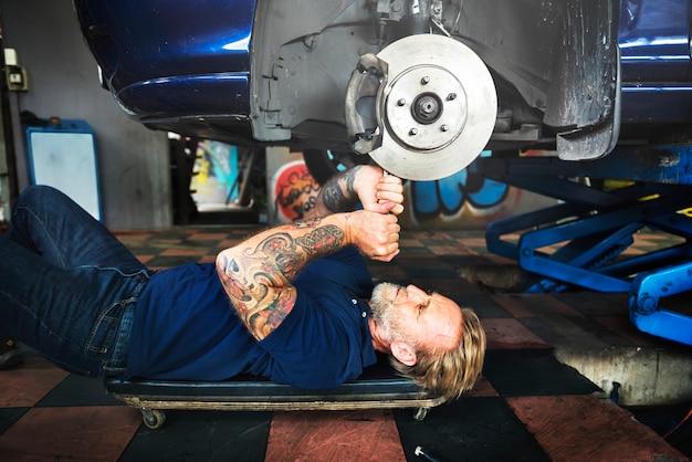 Kaukasischer automechanikermann, der rearing auto-scheibenbremse in der garage liegt