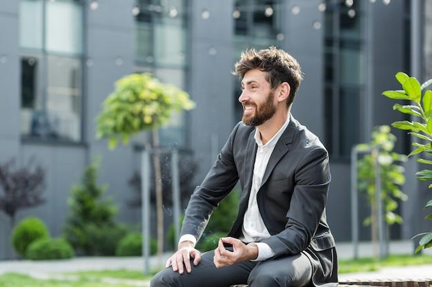 Kaukasischer bärtiger geschäftsmann, der cannabis im freien raucht, sitzt auf der stadtparkbank auf städtischem straßenhintergrund. männlicher angestellter geschäftsmann. büroangestellter im anzug lindert stress ein marihuana draußen