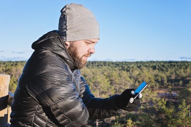 Kaukasischer bärtiger mann, der smartphone gegen blauen himmel betrachtet