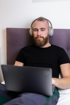 Kaukasischer bärtiger mann in den kopfhörern im schlafzimmer auf dem bett, das vom laptop von zu hause aus arbeitet, tippt, denkt.