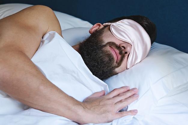 Kaukasischer bärtiger mann in der augenmaske, die im bett schläft