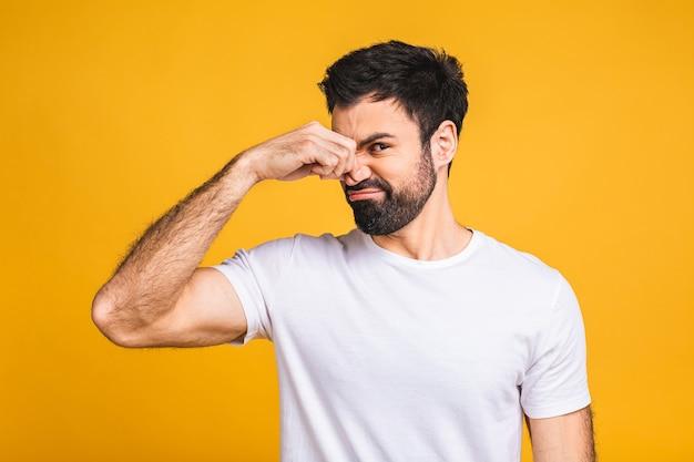 Kaukasischer bärtiger mann isoliert über gelbem hintergrund, der etwas stinkendes und ekelhaftes, unerträgliches riechen riecht