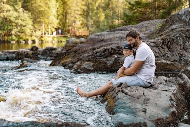 Kaukasischer bärtiger vater und sein süßer kleiner sohn sitzen auf einem großen felsen am bergfluss-riss einweichen ...