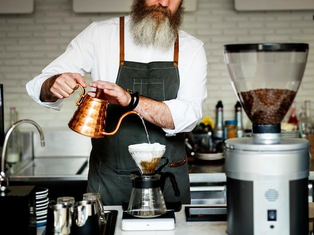Kaukasischer baristamann, der tropfenfängerkaffee bildet