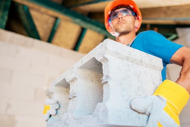 Kaukasischer bauarbeiter mit betonblock