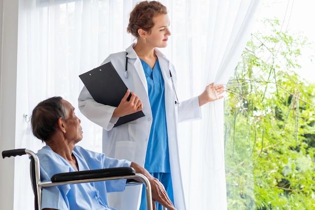 Kaukasischer berufsarzt der frau, der mit patient im krankenzimmer beruhigt und bespricht.
