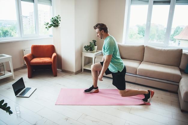 Kaukasischer blonder sportlicher mann benutzt einen laptop, während er zu hause fitnessübungen macht