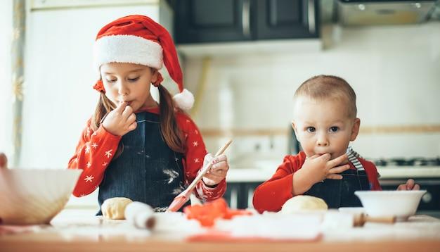 Kaukasischer bruder und schwester bereiten essen für die weihnachtsferien vor, die santa kleidung in der küche tragend tragen
