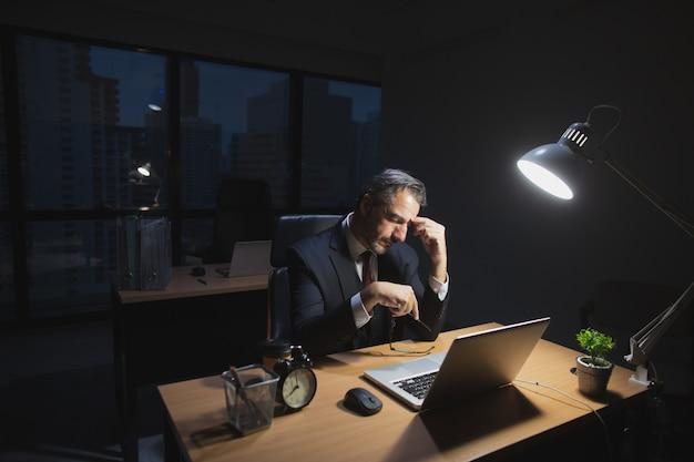 Kaukasischer chef, der spät arbeitet, sitzend auf schreibtisch im büro nachts. geschäftsmann, der für überlastungsjob-griffgläser und -hand auf nase müde und druck sich fühlt