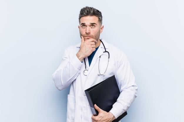 Kaukasischer doktormann, der den ordner seitlich schaut mit zweifelhaftem und skeptischem ausdruck hält.