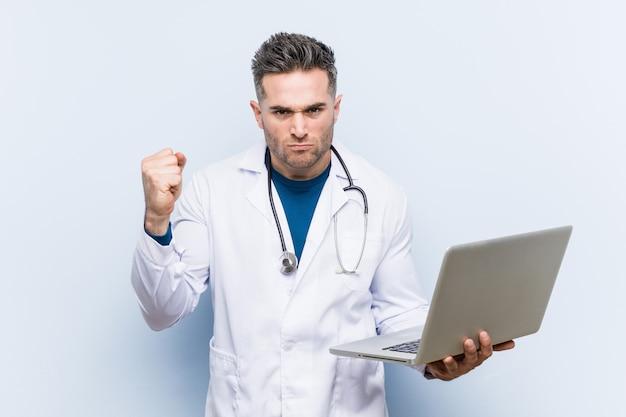 Kaukasischer doktormann, der einen laptop zeigt faust zur kamera, aggressiver gesichtsausdruck hält.
