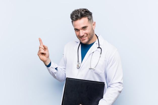 Kaukasischer doktormann, der einen ordner lächelt hält, freundlich zeigend mit dem zeigefinger weg