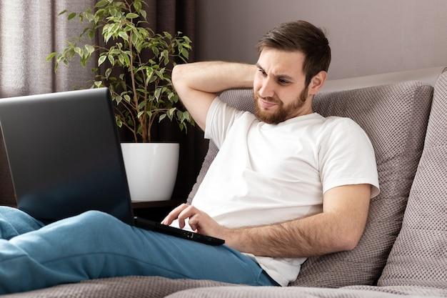 Kaukasischer düsterer mann des stresses im stress, der vom hauptbüro unter verwendung des laptops arbeitet. heimarbeit