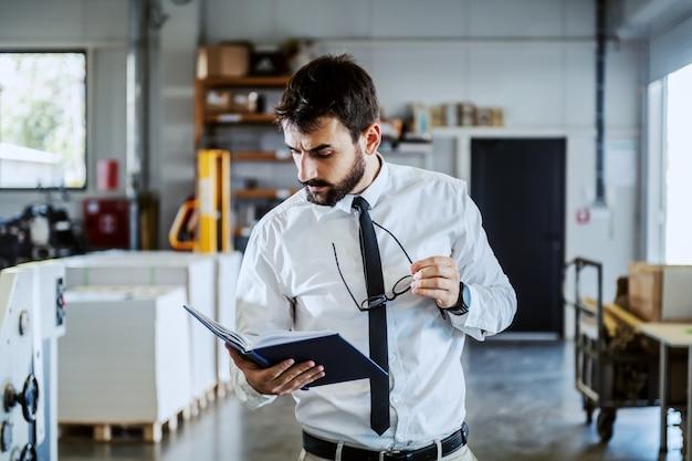 Kaukasischer ernsthafter grafiker in hemd und krawatte, hält notizbuch und betrachtet es, während in druckerei stehend.