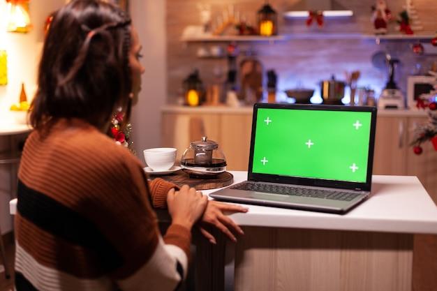 Kaukasischer erwachsener, der laptop-computer mit grünem bildschirm betrachtet