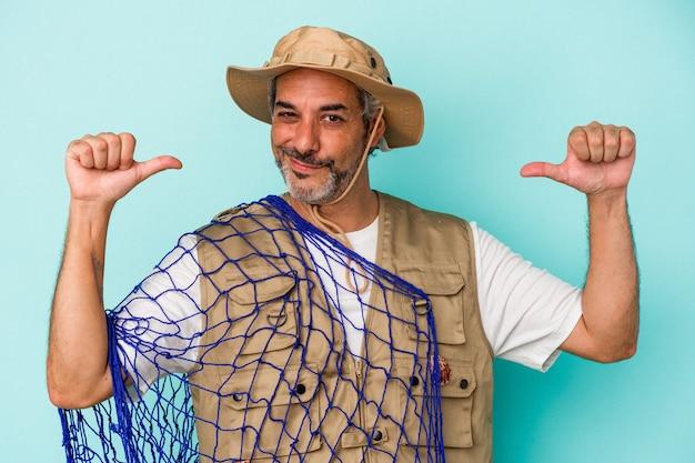 Kaukasischer fischer mittleren alters, der ein auf blauem hintergrund isoliertes netz hält, fühlt sich stolz und selbstbewusst, beispiel zu folgen.