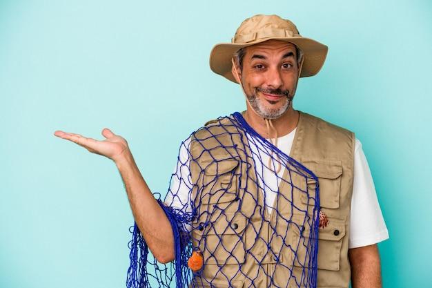 Kaukasischer fischer mittleren alters, der ein netz isoliert auf blauem hintergrund hält, das einen kopienraum auf einer handfläche zeigt und eine andere hand an der taille hält.