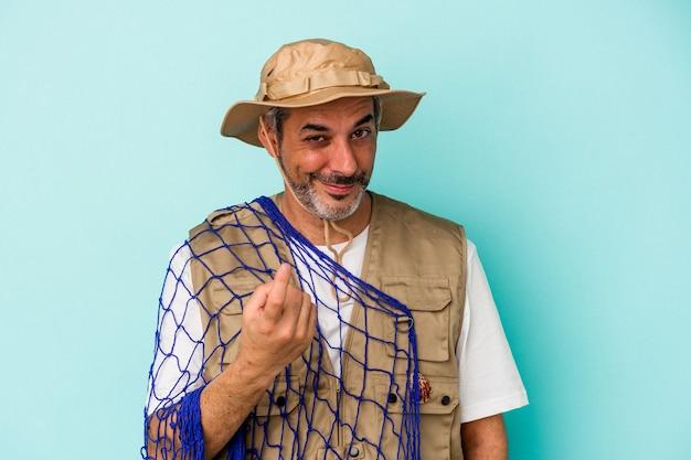 Kaukasischer fischer mittleren alters, der ein netz isoliert auf blauem hintergrund hält und mit dem finger auf sie zeigt, als ob sie einladen würden, näher zu kommen.