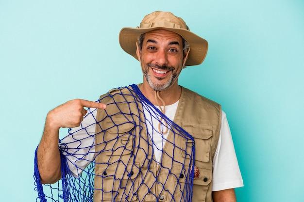 Kaukasischer fischer mittleren alters, der netz einzeln auf blauem hintergrund hält, der mit der hand auf einen hemdkopierraum zeigt, stolz und selbstbewusst