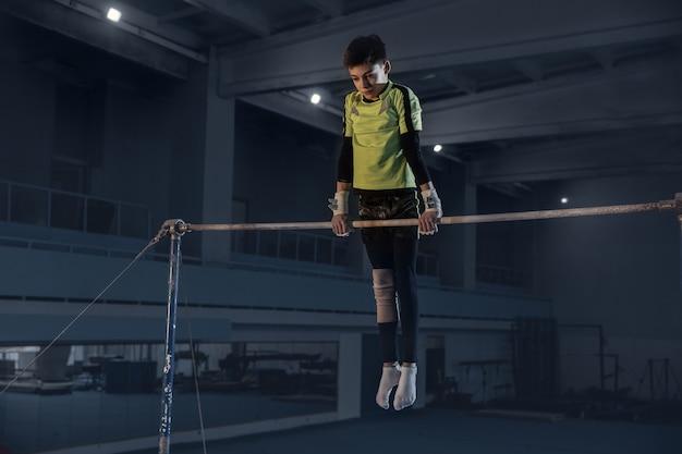 Kaukasischer fit kleiner junge, athlet in der sportbekleidung, die in übungen für kraft, gleichgewicht übt.