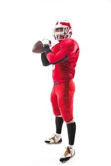 Kaukasischer fitness-mann als american-football-spieler, der einen ball auf weißem hintergrund hält
