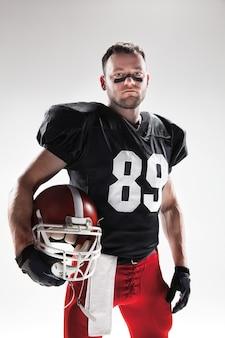 Kaukasischer fitnessmann als amerikanischer fußballspieler auf weißem hintergrund