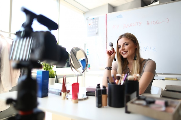 Kaukasischer frauen-blogger, der schönheits-video-blog erstellt. weibliche maskenbildner-aufnahme-kosmetik wenden spitzen an.