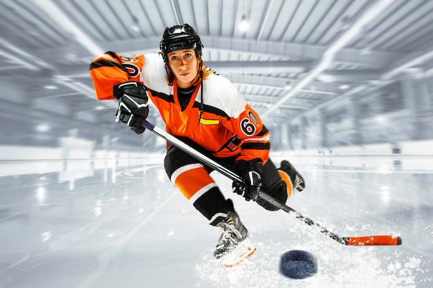 Kaukasischer frauenhockeyspieler, der eis schiebt, tritt auf.