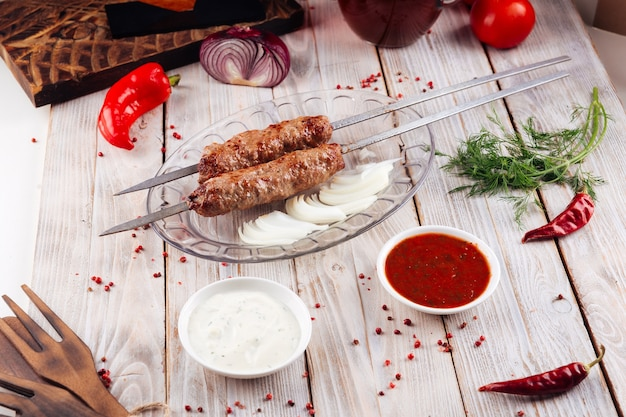 Kaukasischer gegrillter fleischspieß lula kebab auf dem hellen holztisch