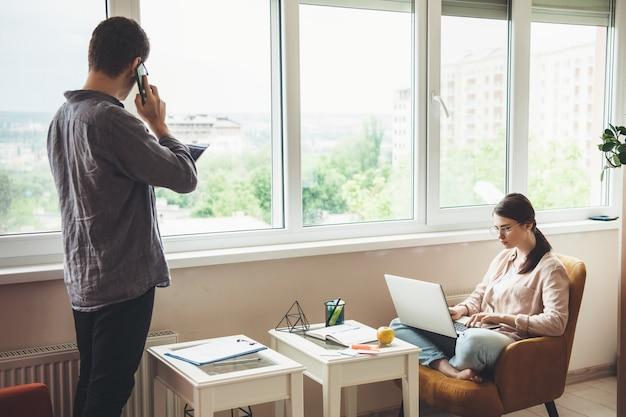 Kaukasischer geschäftsmann, der am telefon diskutiert, während seine freundin am laptop arbeitet und im sessel sitzt